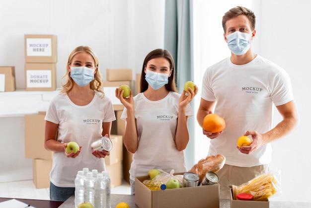Вид спереди добровольцев в медицинских масках, готовящих пожертвования на еду Бесплатные Psd