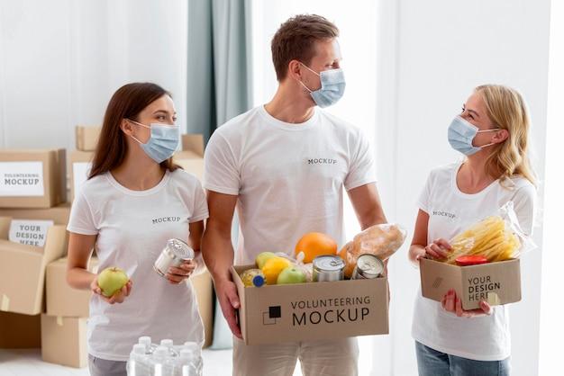 Вид спереди добровольцев в медицинских масках, готовящих пожертвования на провизию Бесплатные Psd