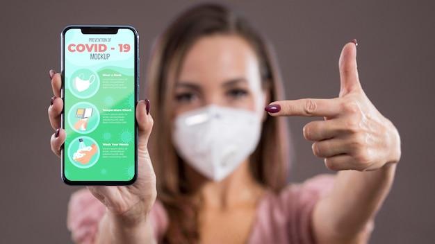 Вид спереди женщины с маской, держащей и указывающей на смартфон Premium Psd