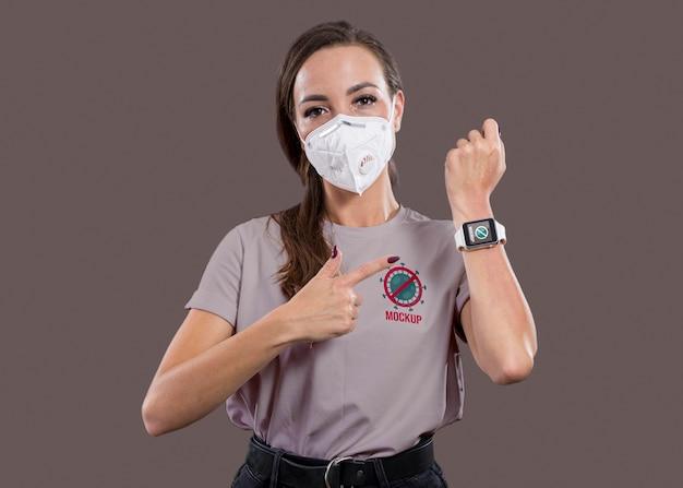 Вид спереди женщины с маской, указывая на умные часы Бесплатные Psd