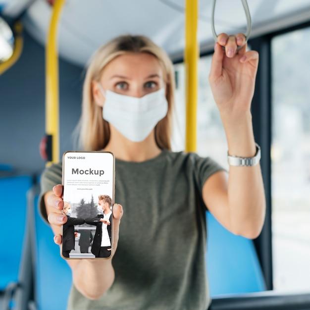 Вид спереди женщины с медицинской маской в автобусе, подняв смартфон Бесплатные Psd