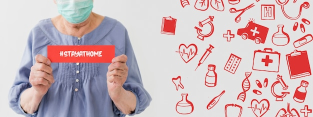 Front view of older woman with medical mask holding message Free Psd
