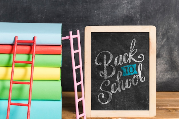Front view pile of books with chalkboard Free Psd