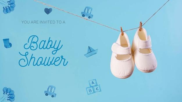 Vista frontale di scarpe e invito per baby shower Psd Gratuite