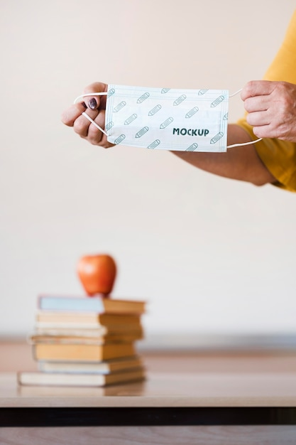 Front view of teacher holding medical mask Premium Psd