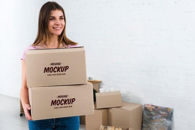 Vista frontale della donna che tiene il modello di scatole per il trasloco Psd Gratuite