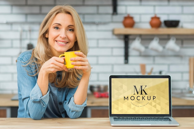 Front view of woman in the kitchen with coffee and laptop Free Psd