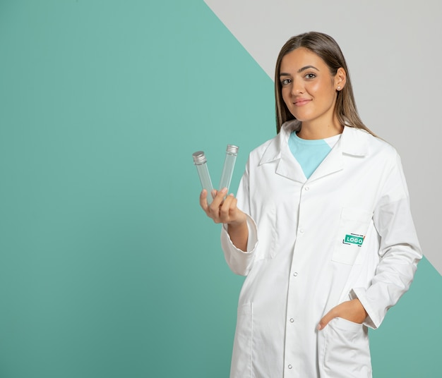 Front view of woman wearing lab coat and holding test tubes Free Psd