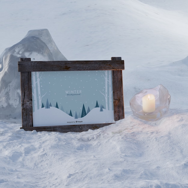 Frozen candle beside frame with winter theme Free Psd