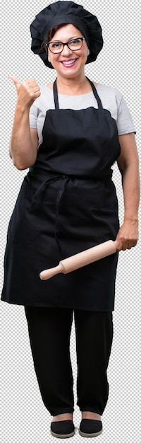Full body middle aged baker woman cheerful and excited, smiling and raising her thumb up, concept of success and approval, ok gesture Premium Psd