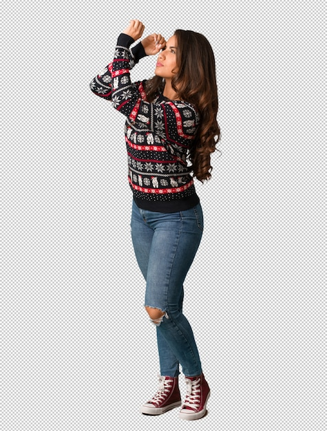 Full body young woman wearing a christmas jersey making the gesture of a spyglass Premium Psd
