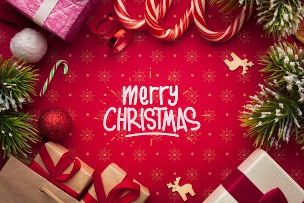 Подарочные коробки и леденцы на красном фоне рождество Premium Psd