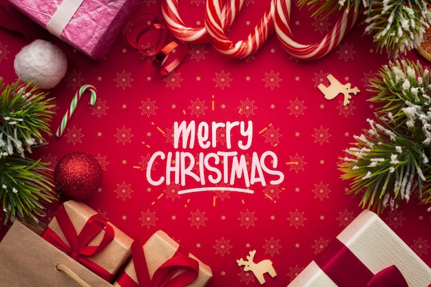 Gift boxes and candy canes on christmas red background Free Psd