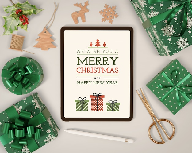 Gifts wrapped beside tablet mock-up Free Psd