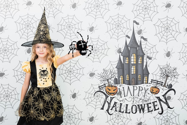 Girl dressed as a witch showing a spider Free Psd