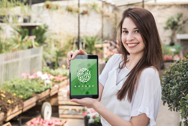 Girl holding tablet mockup with gardening concept Free Psd