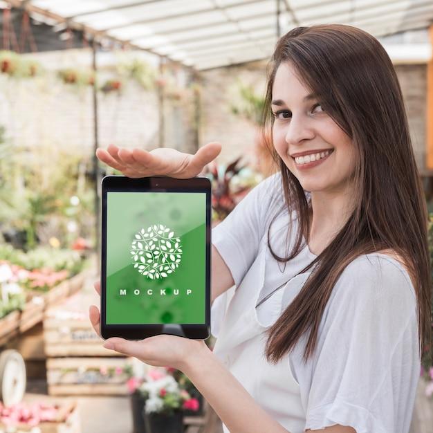 Девушка держит планшет макет с садоводством концепции Бесплатные Psd