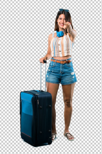 Girl traveling with her suitcase points finger at you with a confident expression Premium Psd