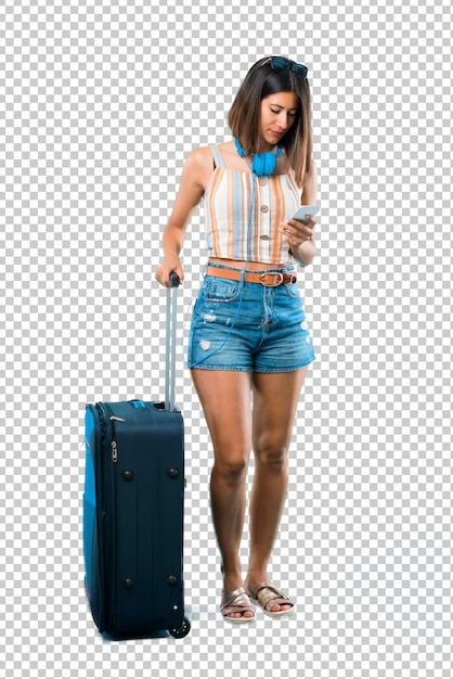 Girl traveling with her suitcase sending a message or email with the mobile Premium Psd