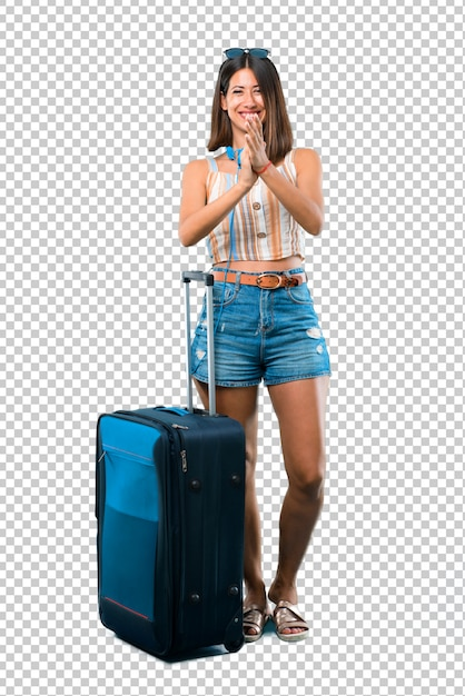 Girl traveling with her suitcase smiling and applauding Premium Psd