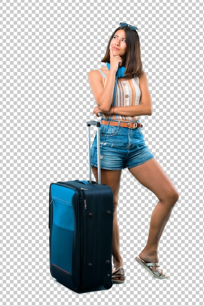 Girl traveling with her suitcase standing and thinking an idea while looking up Premium Psd