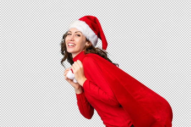 Girl with christmas hat holding a christmas bag full of gifts Premium Psd
