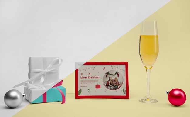 Glass of champagne next to a frame with mock-up Free Psd