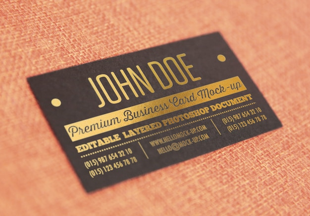 Gold letterpress on black paper business card template mockup on textile type surface