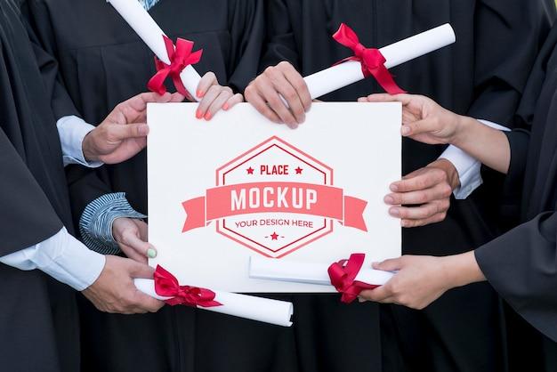 Graduates holding a mock-up diploma Free Psd