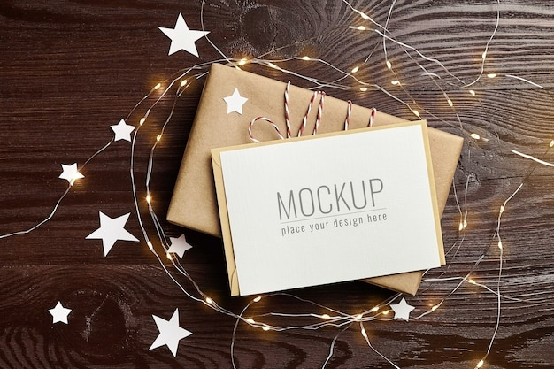 Greeting card mockup with gift box and christmas lights on wooden table Premium Psd