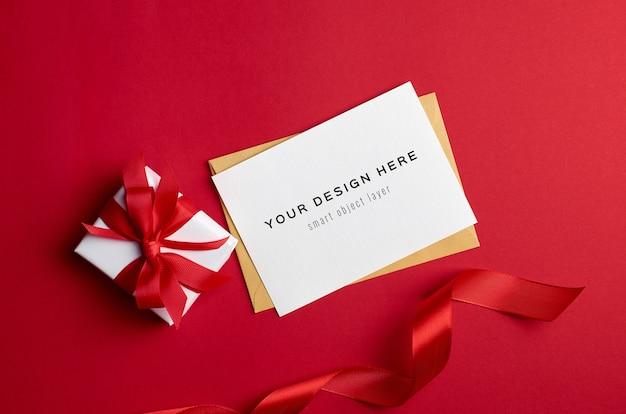 Макет поздравительной открытки с подарочной коробкой на красном фоне Premium Psd