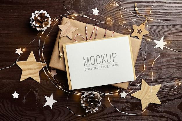 Макет поздравительной открытки с подарочной коробкой, сосновыми шишками, деревянными украшениями и рождественскими огнями Premium Psd
