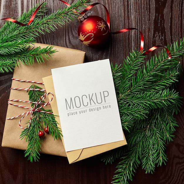 선물 상자, 빨간 크리스마스 공 및 전나무 나무 가지와 인사말 카드 모형 프리미엄 PSD 파일