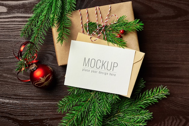 Greeting card mockup with gift box, red christmas ball and fir tree branches on wooden table Premium Psd