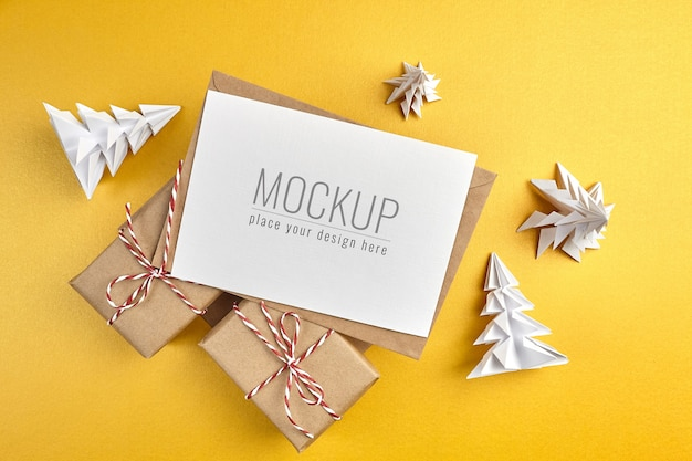 선물 상자와 골드 배경에 종이 크리스마스 트리 인사말 카드 모형 프리미엄 PSD 파일