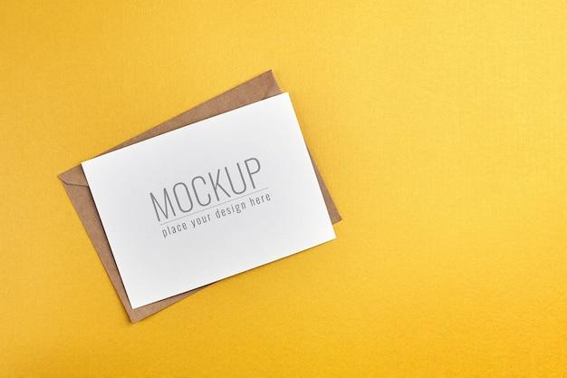 金の紙の背景に封筒のモックアップとグリーティングカード Premium Psd