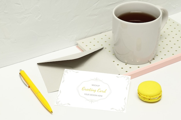 Greeting card  with notes, envelope, pen, macaron and cup of tea Premium Psd