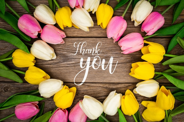 Greeting template with tulips on a wooden background Free Psd
