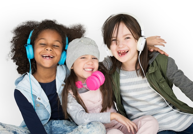 Group of little girls studio smiling wearing headphones and winter clothes Premium Psd