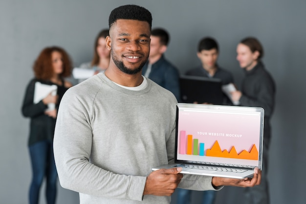 Group of people holding laptop mockup for charity Free Psd
