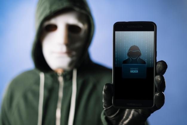 Hacker segurando celular infectado por malware hackeado