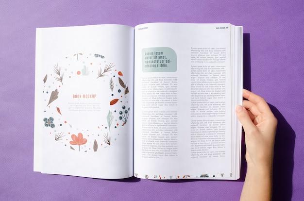 Hand holding a magazine on purple background Free Psd