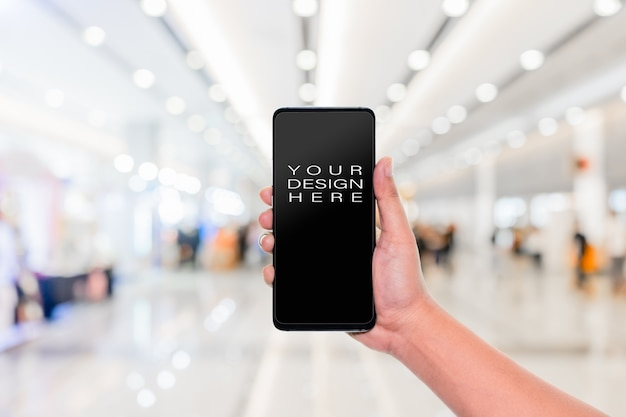 Hand holding mobile phone with blur corridor hall way Premium Psd