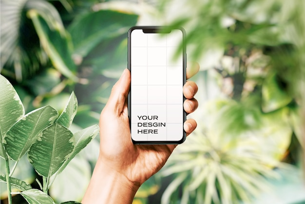 Hand holding new smartphone mockup surrounded by leaves Premium Psd