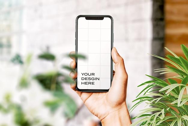 Рука держит новый макет смартфона в окружении листьев Бесплатные Psd