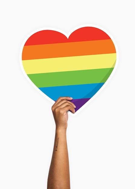 Hand holding a rainbow heart cardboard prop Premium Psd