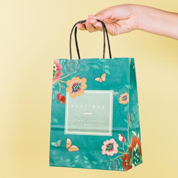 Hand holding shopping bag mockup Free Psd