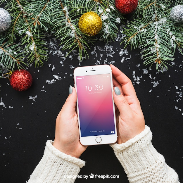 Hand holding smartphone mockup with christmas design Free Psd