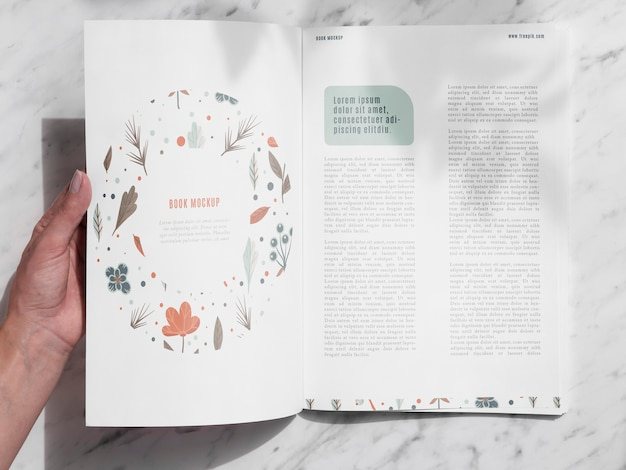 Hand opening a magazine on grey background Free Psd