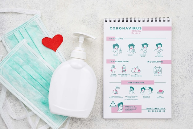 Hand sanitizer and medical masks beside notebook Free Psd